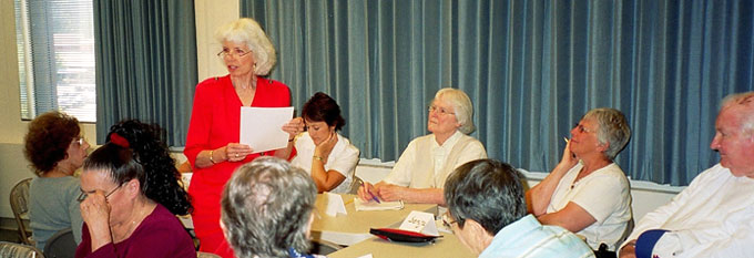 Photo of Nan Phifer standing and talking to a group of eight seated adult students