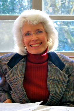 Photo of Nan Phifer, smiling, sitting in front of a window